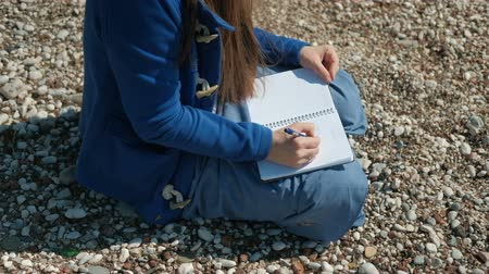 diary : A woman is sitting on a stony beach and writing a pen in the notebook. She is dressed in a blue outfit and prints letters in a beautiful handwriting alone. Her hair is waving from the wind. The sun illuminates the female figure, which is on small stones.  Stock Footage