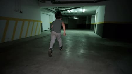 trousers : Little boy runing in underground garage. Child around spacious dimly lit parking lot for cars of about seven years dressed in T-shirt and gray trousers with disheveled hair is having fun. Huge shed is located under territory of high-rise residential compl