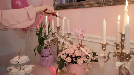 посылка : Womans hand lights wax candles on table in living room. In banquet hall number handsome skied ball have beautifully arranged bouquets of pink roses and tulips as well as light cakes on multi-tiered plate. Preparations are in full swing for celebration of