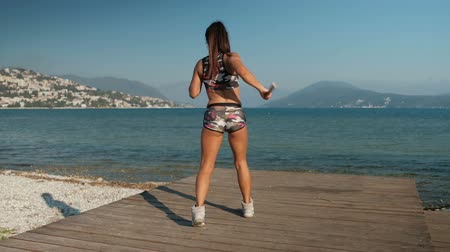 oneperson : The female athlete trains with nunchaku on the timber decking on the seashore. The sportswoman stands a back to us, but she is concentrated, with strong muscles and in her hand is karate stick. Woman is dressed in sportswear such as tube top and shorts in