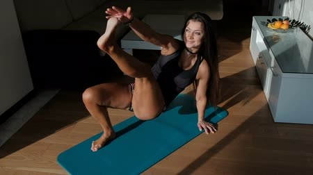 Young confident slim woman doing exercises on blue mat indoors. Beautiful attractive female with long dark hair, bright makeup, slender body, black tight T-shirt, short camouflage shorts, leaning arms and legs, alternately reaches out to heel with one han