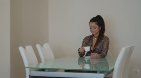 Young peaceful woman sitting on chair and drinking tea indoors. Beautiful slim female with long black hair, gathered in tail, in transparent short dress with brindle print, with pendant on neck, relaxing at home, sits comfortable on white furniture before Стоковые видеозаписи