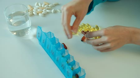 Woman sorts nutritional vitamins in blue tablet box on the week. Female adds one dark pill and three light pills in each cells of container by her hands. Designations of the days of the week is written on the top of box for easy daily use. After putting t Стоковые видеозаписи