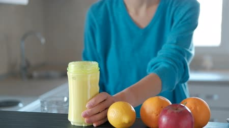 antioxidant : Young woman makes big glass of healthy fruits smoothie at home. Sporty female stands in her kitchen preparing juice from fresh fruits. Then she changes nozzle with blending attachment unscrewing off it on the other for drink and takes bottle of fruit yell
