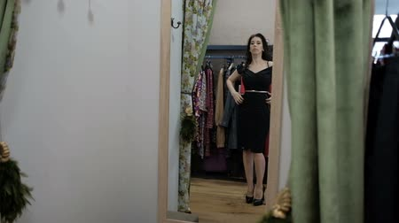 A woman in a dressing room on high heels is measuring a black dress. A tall brunette in stylish shoes picks up an evening outfit for a date. She evaluates her reflection in the mirror and adjusts the waistband. Behind is a long coat rack with different cl