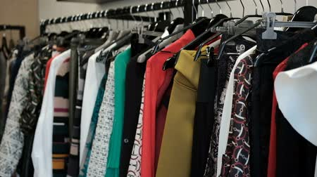 šatník : The clothes hanging on the hanger are different in style and texture. Womens clothing hangs on a metal stand. The set consists of yellow, red and gray outfits for everyday wear. In the store during the sale a collection for the promotion was collected. Th