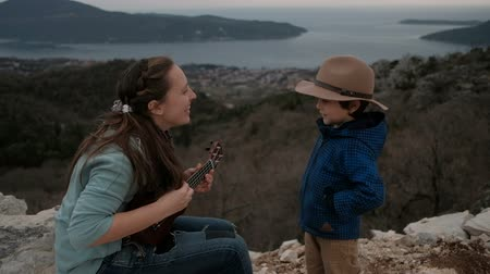 Woman playing guitar and little boy on cliff in overcast day. Brunette dressed in jacket and jeans and her cute son in beige hat spend time on rocks in cool summer weather against backdrop blue sea and distant green mountains shrouded in fog. Mom ferventl