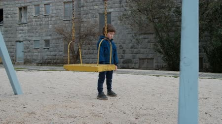 Little boy standing near swing in playground outdoors. Pensive boy dressed in blue jacket, black pants and boots spends his time on sandy sport ground where he is alone. He is located near swinging yellow carousel on background of gray stone building and  Wideo