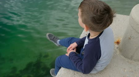ás : Little boy dangles his legs sitting of the side a pier. Dark child looks out to sea and switches one s head round, hands folds on his legs. He is dressed in sweater, dark blue trousers and gym shoes. Bead from wood is on kid s neck. Water is blue-green, w Stock Footage
