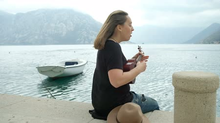 Young woman playing guitar sitting on pier sea in summer day. Brunette dressed in black t-shirt and jeans rested comfortably on platform off coast her legs hanging down. She enjoys spending time at the waters edge against backdrop turquoise waves, seen in Wideo