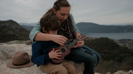 Mother teaches son to play guitar sitting together on the coast on a stone. Brunette woman shows her child how to plunk a ukulele and little boy repeats her motion arm. Instrument has four strings and makes of wood. They are dressed warmly it is murky day
