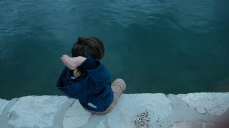 Little boy sitting on pier throws stones into water outdoors. Cute child dressed in blue jacket and beige trousers spends warm autumn day turning to face aqua on concrete platform hanging his legs down. Next to him lies bunch of small gray calculus that h Стоковые видеозаписи