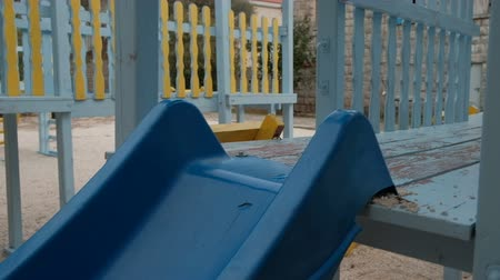 Little boy rides down a plastic slide on the playground in cool day. Kid plays alone, he runs fast to blue slippery dip and climbs up on it wooden yellow stairs. Then child holds on with rope, sits a side sliding down. Cute boy is calm, collected and not