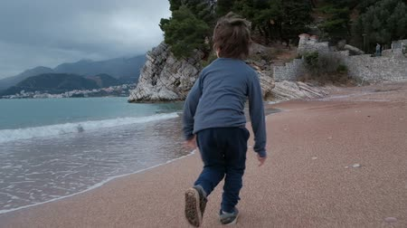 Little boy runs fast alone along sandy seacoast of bay. Traces of kid feet are seen on the wet sand, he runs aside massive masonry wall. Child lobs along, his feet sticks in the sand. Wind ruffles his dark hair. Boy is dressed warmly it is cool day with c Стоковые видеозаписи