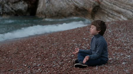 Little boy meditating sitting by sea outdoor. Child wearing blue jacket and black pants is conveniently located on small stones at the waters edge on cloudy summer day. He especially likes to practice while being on picturesque nature away from city under Стоковые видеозаписи