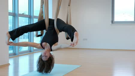 Young woman hanging upside down in hammock for yoga indoors. She slowly swings body with her legs wide apart and holds them with her fingers then she fully straightens and leans her hands on floor. Fitness lady dressed in black sportwear with naked feet v Стоковые видеозаписи