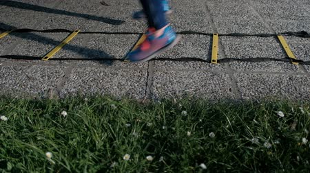A human being in sneakers jumps through rods with ropes on the asphalt. The athlete in sports uniform on socks jumps and puts stops together, and then apart. Exercise is carried out for the entire length of the sports equipment. Next to it, a green grass