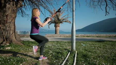 Young woman practicing lunges with TRX loops outdoor. Brown-haired in sports t-shirt, pants and sneakers performs exercise to strengthen buttocks and hamstrings. She works on green lawn near home with beautiful view of ocean and palm trees. Holding tightl