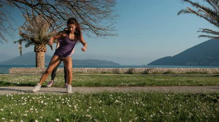 Two women in sports clothes doing lunges in outdoor. Young athletes in purple T-shirts work out on green grass against blue sea, rocks and tall palm trees. Brown-haired female stands behind brunette, on exhalation they make step to side bending knee and t