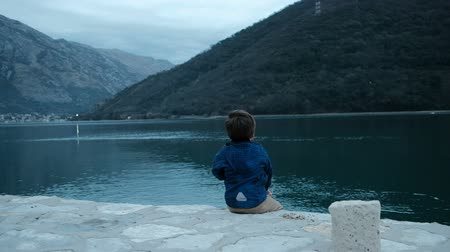 Little boy sits on shore and throws stones into water outdoors. Cute child, dark-haired, dressed in blue jacket, sitting on concrete beach and alternately throws pebbles neatly putted next to him. Kid likes new occupation, throwing pebble as far as possib