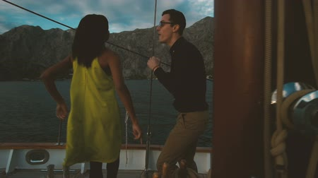 Romantic traveling of loving couple dancing on yacht outdoors. Beautiful woman with dark skinned hair yellow dress smiling dance enjoy music. man in shirt trousers looks at wife moving body. expensive ship deck on waves family singing spending evening tog