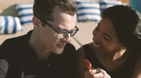 Two young people laugh and eat strawberries outdoors. Close-up view on faces of happy couple. Attractive dark-haired man in black T-shirt and glasses, tells interesting story to girlfriend, smiling. Beautiful black-skinned girl, metis, with straight hair,