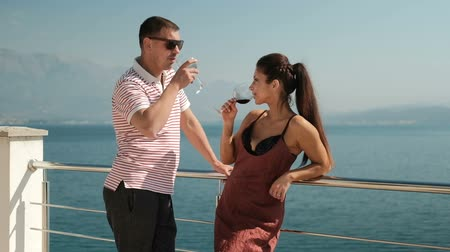 Couple in love standing on loggia and drinking wine and communicate. Tall man, in glasses, t-shirt and trousers, stands near iron railing, holds alcoholic drink in glass and talks interesting story to beautiful wife. Pretty slim woman, with black long hai
