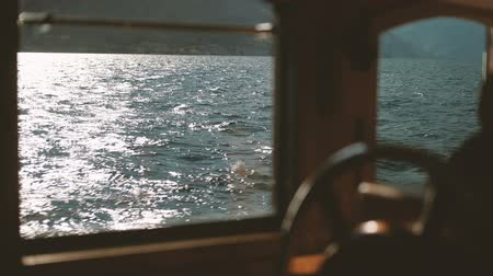From the yacht window you can see the sea in which the sun reflects. The captain stands at the controls and guides the ship across the blue ocean. In sunny weather, tourists make a sea voyage on the waves, in which the rays are seen at sunset. A beautiful Стоковые видеозаписи