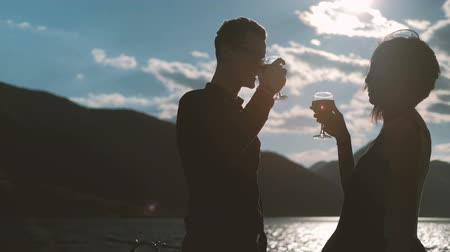nápoj : Young couple drinking wine standing on beach on summer day. Man with glasses and woman dressed in black silk gown waving by light wind located near water against backdrop of glowing turquoise waves and majestic mountains in distance. Beautiful lovers enjo