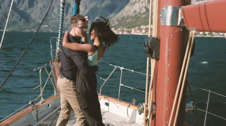 Loving happy couple dancing on yacht walk on lake outdoors. Beautiful woman with dark skinned hair black skirt blue topic smiling hugs man in shirt trousers looks at wife leads in dance. expensive ship deck on waves. Sun rays, penetrating water, reach bot