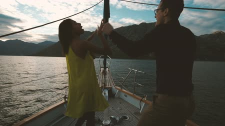 Young woman and man dancing on deck of ship in evening outdoors. Beautiful couple in love rhythmically move under cheerful music standing on wooden floor of small vessel moving along calm waves of Adriatic Sea along green picturesque mountains. Tanned bru Стоковые видеозаписи