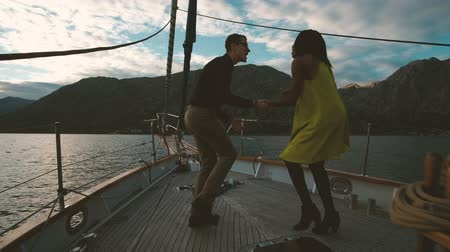 Romantic loving couple dancing on yacht sunset outdoors. Beautiful woman with dark skinned hair mulatto yellow dress smiling dance enjoy music. man in shirt trousers looks at wife moving body. Shooting down expensive ship deck on waves family singing spen