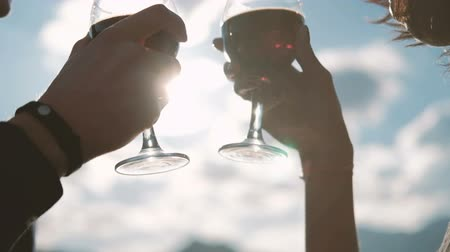 Man and woman are drinking wine in glasses against the blue sky. Couple spend a romantic evening outdoors. Young people who are in touch with each other celebrate an important event in their family life. With their hands, they hold the glass vessel by the