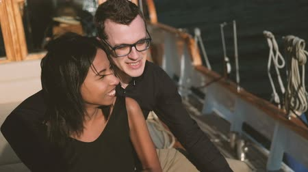 A man and a woman are sitting side by side and talking on a yacht. A dark-skinned young lady with black hair listens as a white guy in stylish glasses tells interesting stories from his life. They sail on a sea voyage in sunny weather at the resort. Peopl