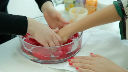 Woman sit on procedure for care hands in spa salon. Specialist puts arms of client into liquid poured into transparent container that contains red rose petals and gently bathes them. Two lady is located at white table in premise with lot of cosmetics prod