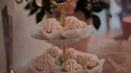 Close-up shot of cakes with cream capcake on festive table. Closeup shooting of Multi-tiered vase with cupcakes with pink protein custard standing on white tablecloth. On background unfocused flower bouquet. rose arrangment on served banquet. preparing fo