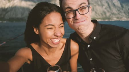 Young man and woman cheerfully doing selfie on ship in open air. Couple in love with glasses of red wine in their hands laughs cheerily, fools around and make faces to camera taking photo with help of selfie-stick which is held by female standing on deck. Стоковые видеозаписи