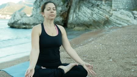 An adult woman sits in a lotus position on the beach near stone rocks. Person meditating eyes closed, with hands on knees with mudras. In the fresh air, the model demonstrates a relaxing asana, which is used for meditation in Hindu yoga and Buddhist conte