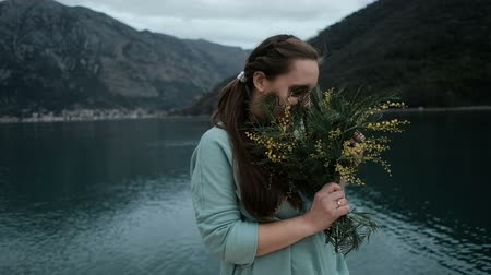 Young woman holds bouquet of mimosa, inhales fragrance near lake. Beautiful lovely woman with long fair-haired hair with braid, in turquoise sweater stands near river, outdoors, enjoys pleasant smell of bunch of flowers in hands, presented by husband or b