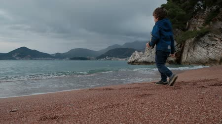 Little boy plays with waves on seashore outdoors. Cute child, dark-haired, dressed in blue jacket, trousers, standing on sand of beach, waiting for waves approach him and running briskly, not soak the shoes. Kid likes new occupation, playing without frien