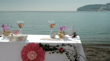table by sea with sweet things snacks, drinks for banquet on fresh air outdoors. On white tablecloth decorating with red paper flower dishes, vases with decoratios, various plates Covered with colorful napkins with candies. preparation for Tea-bahquet for
