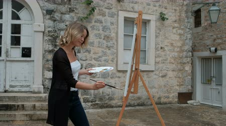 Woman painter paints picture on easel standing outdoors. Smiling lady draws gouache with black brush on white canvas that is in front of her and occasionally looks at old stone building near which stands. Female dressed in white top and black sweater is k Стоковые видеозаписи