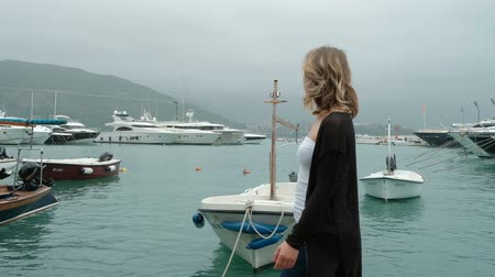Woman with blond hair looking at various yachts in the marina. In cloudy weather, a slender lady walks leisurely along the shore, on which small boats and large boats are moored. Berth is specially equipped for the vehicles on which the crew provided a va Стоковые видеозаписи