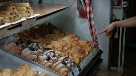 индекс : Woman shows a finger on a baking pastry choices. In a bakery on a show-window various kinds of pies and pastries on which the price list with the price in euro is specified is presented. Female hand index finger points to the seller on the kind of dessert