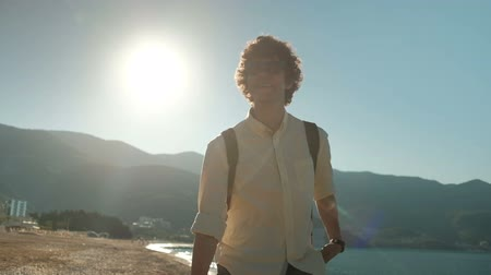 duygusal : Smiling man strolls along beach on summer morning. He is in good mood going slowly along deserted coast, enjoying warm weather and peaceful atmosphere of sea irrigated by turquoise waves. Curly-haired man in sunglasses dressed in shirt and jeans prefers t Stok Video