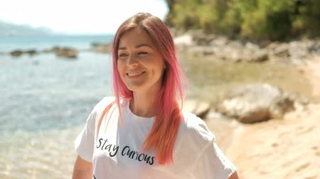 computação gráfica : Portrait of a beautiful woman with pink hair on a summer beach. Near the shore stands an adult lady, who smiles and looks around. She rejoices and rejoices. Her positive mood in the fresh air. Person wearing a white T-shirt with black lettering. Around gr