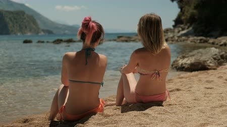 két : Two beautiful women are sitting on a sunny beach and talking. Attractive ladies rest on the sand