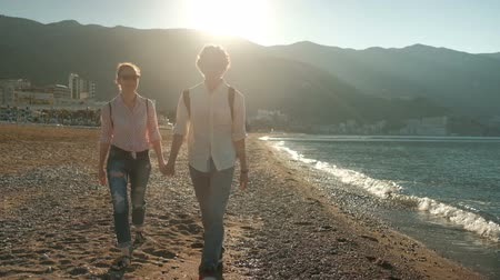 沿岸の : Young couple walking along seashore in summer day. They are holding hands, slowly goes over sandy coast, talk about something nice and kiss each other. Attractive woman in sunglasses dressed in pink s 動画素材