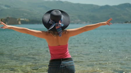 tutum : Woman in hat standing on the shore happily flinging arms to the side. She stands with her back and with pleasure breathes in the smell of the sea. Excellent sunny weather contributes to a positive attitude and rest during your stay at the resort. An elega