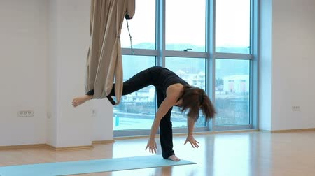 életerő : Attractive woman practices gravity yoga in studio indoors. She stands, one leg in fabric loop of hammock, leans hands on floor